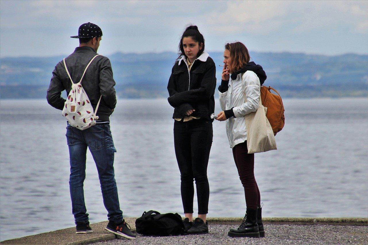 młodzież nad jeziorem w jesiennych kurtkach
